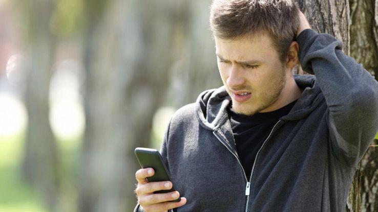Un ragazzo infastidito mentre usa il telefono