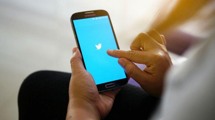 Un uomo tiene in mano lo smartphone mentre accede a Twitter