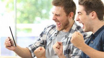 Due ragazzi esultano mentre guardano una partita su un tablet