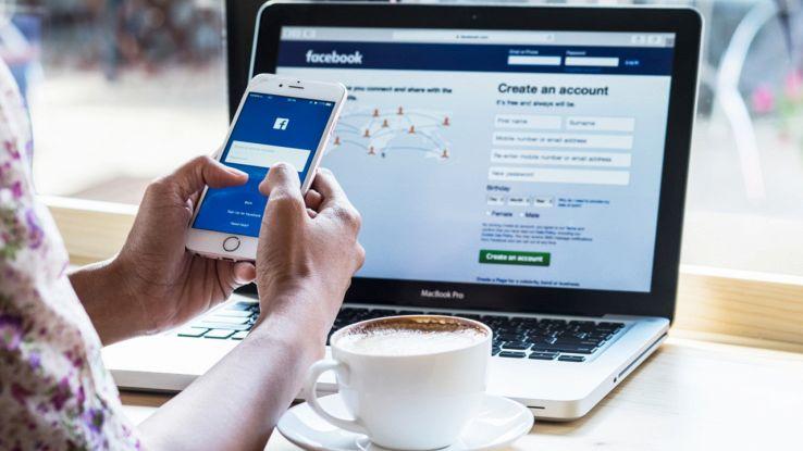 Una ragazza usa Facebook da smartphone e PC