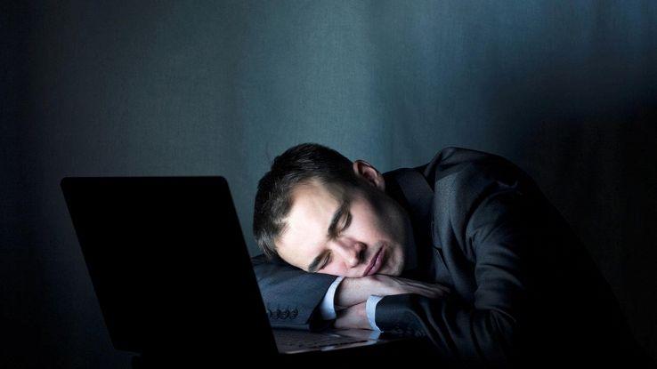 uomo che dorme davanti a pc acceso