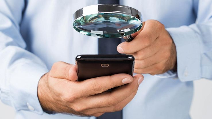 uomo con lente d'ingrandimento spia uno smartphone