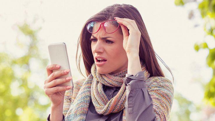 ragazza guarda schermo smartphone con faccia attonita
