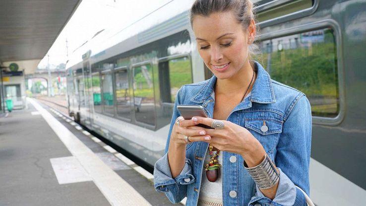 Ragazza con smartphone vicino al treno