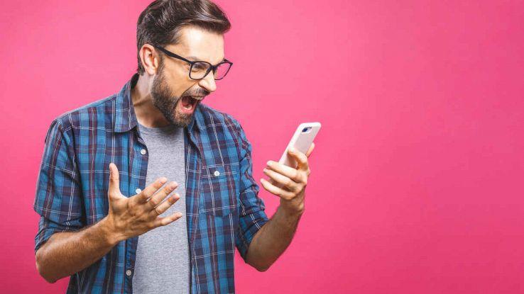 Uomo arrabbiato con smartphone tra le mani