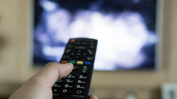 uomo con telecomando davanti al tv