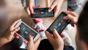 Tre ragazzi giocano con lo smartphone