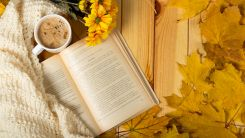 Su tavolo in legno, visti dall'alto, da sx a dx, un libro aperto, una coperta di lana color avorio, fiori gialli finti, foglie marroncine autunnali