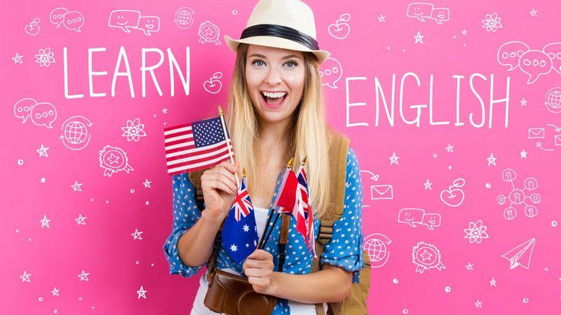 Una turista bionda, con panama e macchina fotografica, brandisce alcune bandiere del mondo anglosassone. Dietro, su fondo rosa, la scritta Learn English