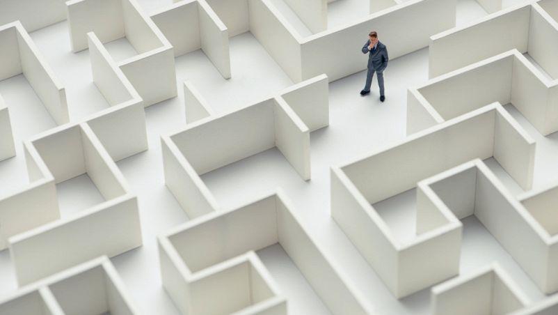 Vista a volo d'uccello di un uomo d'affari intrappolato in un labirinto bianco caratterizzato da molte vie interrotte, perplesso sulla strada da imboccare