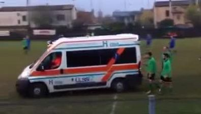 I calciatori spingono l'ambulanza